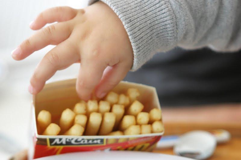 main d'enfant qui prend une frite