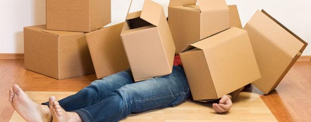 Une personne sous pile de cartons de déménagement