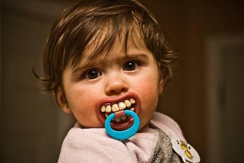 conventions sociales bebe avec sucette qui représente des dents